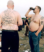 Two topless men drinking beer standing in crowded field.