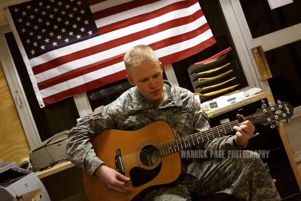 IRAQ, BAGHDAD - JUNE 27: Cpt. Andrew Betson (25), Alpha Company, 4th Battalion, 6th Armoured, 4th Brigade, 3rd Infantry Division, of Midway, Georgia, plays his guitar in the combat outpost in the suburb of Sadiyah, June 27, 2008 in Baghdad, Iraq. Neighbourhoods like Sadiyah became a battleground for Shiite militias and Sunni extremists after the bombing of the Golden Mosque in Samarra in 2006. Tens of thousands of people were either forced out of their homes or fled the violence to neigbouring countries or other parts of Iraq. Now predominantly Shiite, Sadiyah is being used as a test case by the Iraqi government to encourage the millions who have fled - many of which have the skills and money to rebuild the country. Since early 2008, Iraq's security situation has improved with oil production is increasing, record government surplus and easing sectarian tensions. (Photo by Warrick Page)