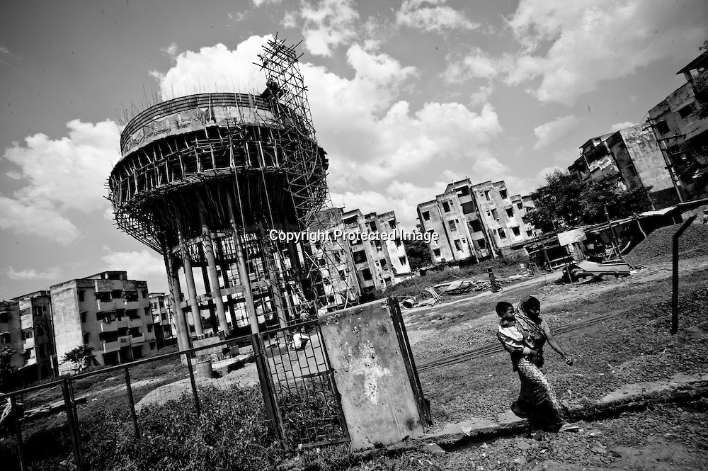 Bhopal, twenty-five years later..A woman carries her child as she walks under a water tower under construction in the city of Bhopal in the state Madhya Pradesh, Indai October 10, 2009. ..Twenty-five years after a gas leak in the Union Carbide factory in Bhopal killed at least eight thousand people, toxic material from the 'biggest industrial disaster in history' continues to affect Bhopalis. A new generation is growing up sick, disabled and struggling for justice...The effects of the disaster on the health of generations to come, both through genetics transferred from gas victims to their children and through the ongoing severe contamination, caused by the Union Carbide factory, has only started to develop visible forms recently...