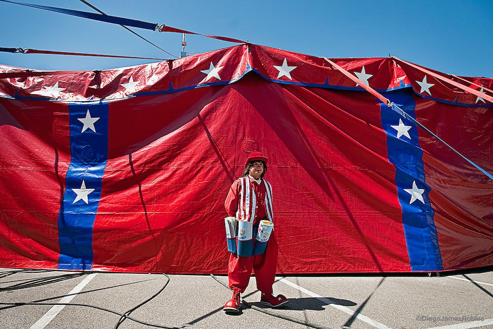 With an apron full of coloring books, Marquino, a veteran clown from Venezuela, waits outside the tent on Sunday afternoon, March 29, 2009. For the part of the show he sells the official Carson & Barnes Circus coloring book inside center ring. All artists, entertainers, clowns and vendors receive a percent of the money they make selling circus merchandize and concessions.