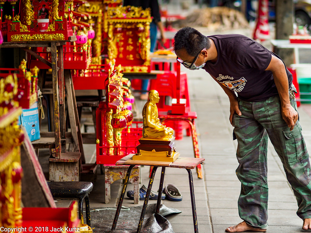 31 JULY 2018 - BANGKOK, THAILAND:  An artisan on Phlap Phla Chai Road in Chinatown looks at a statue of a revered Buddhist monk he just finished painting. Bangkok's Chinatown district is one of the largest Chinatowns in the world. It was established in 1781 when Siamese King Rama I gave the Chinese community in Bangkok land outside of Bangkok's city walls so he could build his palace (what is now known as the Grand Palace). Chinatown is now the heart of the Thai-Chinese community. About 14% of Thais have Chinese ancestry.   PHOTO BY JACK KURTZ