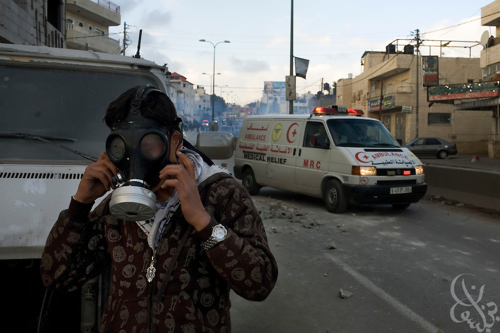 A Palestinian protester adjusts his gas mask as a Red Crescent ambulance makes its' way past during clashes with The Israeli Defense Forces and Police January 09, 2009 in the West Bank at the Kalandia Crossing. Across the West Bank today there were a number of protests against the Israeli incursion into Gaza which has entered its 14 day.