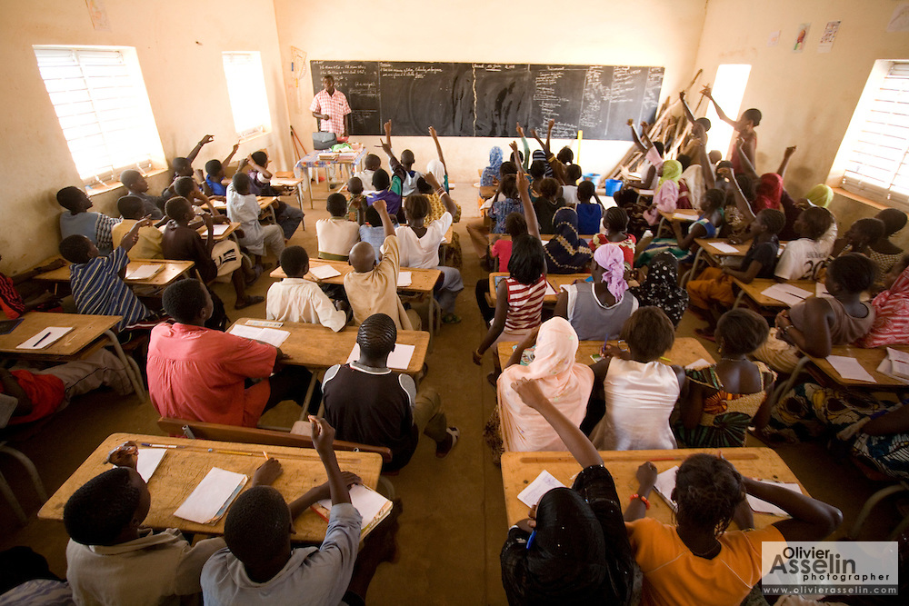 Children raise hands to answer a question during class at the Tangory Transgambienne 2 primary school in the town of Bignona, Senegal on Wednesday June 13, 2007.