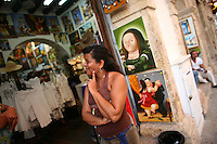 """A woman stands outside of a store selling souvenirs to tourists in the """"Old City"""" in Cartagena, a unique travel destination on Colombia's Caribbean coast. (Photo/Scott Dalton)"""