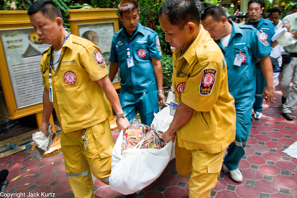 """20 MAY 2010 - BANGKOK, THAILAND: Medical workers and forensics experts recover the bodies of nine anti government protesters in Wat Pathumwanaram near the Ratchaprasong Intersection in Bangkok Thursday. At least some of the nine were so called """"Black Shirts"""" armed fighters who support the Red Shirts. The day after a military crackdown killed at least six people, Thai authorities continued mopping up operations around the site of the Red Shirt rally stage and battle fires set by Red Shirt supporters in the luxury malls around the intersection. They also recovered at least seven bodies from Wat Pathumwanaram, next to Central World mall, which was destroyed by fire. The nine people killed in the temple were not included in the government's body count from Wednesday.    PHOTO BY JACK KURTZ"""