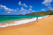 Woman walking along Secret Beach (Kauapea Beach), Island of Kauai, Hawaii USA