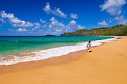 Woman walking along Secret Beach (Kauapea Beach), Island of Kauai, Hawaii USA