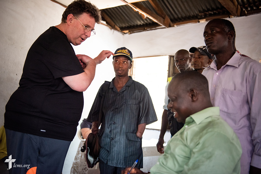 The Rev. Michael Awe, team leader and pastor at Hope Lutheran Church, South Sioux City, Neb., welcomes a man who was a victim of the country's civil war to the clinic on the third day of the LCMS Mercy Medical Team on Wednesday, May 9, 2018, in the Yardu village outside Koidu, Sierra Leone, West Africa. LCMS Communications/Erik M. Lunsford