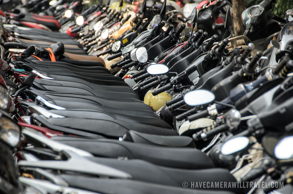 A long row of motobikes and scooters lined up on the side of a street in the Old Quarter of Hanoi, Vietnam.