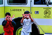 Young boys do their best firemen interpretations as they watch real professionals put out a house fire down the block.