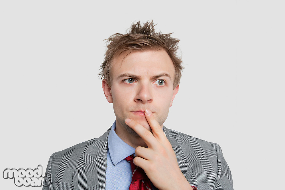 Close-up of young businessman thinking hard over colored background