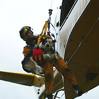 RAF rescue helicopter winchman Neil Finch with rescued dog Jack a four year old cross collie owned by Shona Maxwell (38) and Craig Ross (35) from Edinburgh winch stranded people from their vehicles after a landslide engulfed the A84 north of Lochearnhead<br /><br />Picture by John Lindsay<br />Copyright Perthshire Picture Agency<br />Tel: 01738 623350  Mobile: 07775 852112