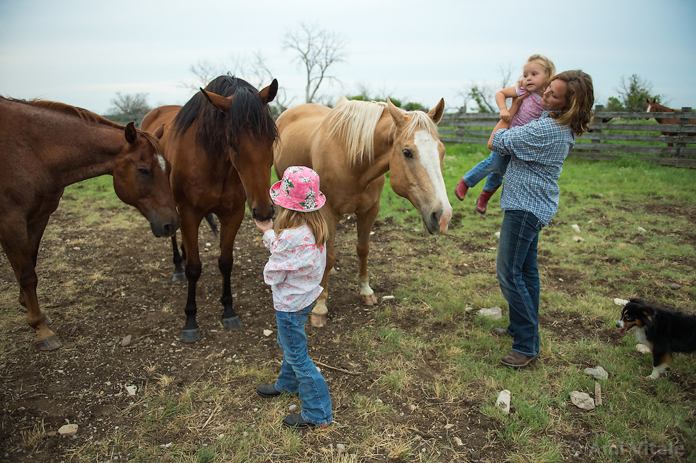 The Nature Conservancy's Matador Ranch Operations Manager Charlie Messerly's wife Jolynn holds her daughter Janae as their other daughter Layla plays with their horses  in Eastern Montana  at the Matador ranch &quot;grass bank&quot;. The &ldquo;grass bank&quot; is an innovative way to leverage conservation gains, in which ranchers can graze their cattle at discounted rates on Conservancy land in exchange for improving conservation practices on their own &ldquo;home&rdquo; ranches. In 2002, the <br /> Conservancy began leasing parts of the ranch to neighboring ranchers who were suffering from  severe drought, offering the Matador&rsquo;s grass to neighboring ranches in exchange for their  participation in conservation efforts. The grassbank has helped keep ranchers from plowing up native grassland to farm it; helped remove obstacles to pronghorn antelope migration; improved habitat for the Greater Sage-Grouse and reduced the risk of Sage-Grouse colliding with fences; preserved prairie dog towns and prevented the spread of noxious weeds. (Photo By Ami Vitale)