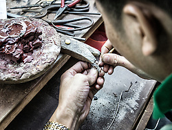 A silversmith works on a piece of jewelry along Hang Bac 'silver street' in Hanoi's Old Quarter, Vietnam, Southeast Asia