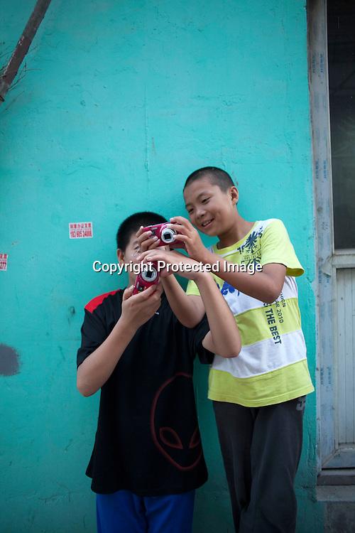 BEIJING, JULY12-14,2013 : Schueler der GAOJIAYUAN Mittelschule fotografieren im Pekinger Bezirk Caochangdi waehrend des Foto Workshops .