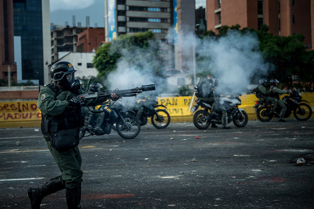 CARACAS, VENEZUELA - MAY 26, 2017: National Guard soldiers fire tear gas, rubber bullets and buckshot at anti-government protesters. The streets of Caracas and other cities across Venezuela have been filled with tens of thousands of demonstrators for nearly 100 days of massive protests, held since April 1st. Protesters are enraged at the government for becoming an increasingly repressive, authoritarian regime that has delayed elections, used armed government loyalist to threaten dissidents, called for the Constitution to be re-written to favor them, jailed and tortured protesters and members of the political opposition, and whose corruption and failed economic policy has caused the current economic crisis that has led to widespread food and medicine shortages across the country.  Independent local media report nearly 100 people have been killed during protests and protest-related riots and looting.  The government currently only officially reports 75 deaths.  Over 2,000 people have been injured, and over 3,000 protesters have been detained by authorities.  PHOTO: Meridith Kohut