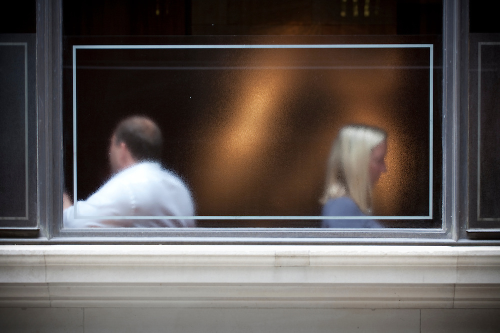 2 people in cafe window obscured by the glass