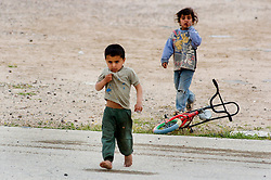 Barefoot Iraqi Children walk across an old car park near the Kuwait border towards British soldiers from The royal Dragoon Guards hoping for handouts from the troops near the Kuwait border during March 2005.