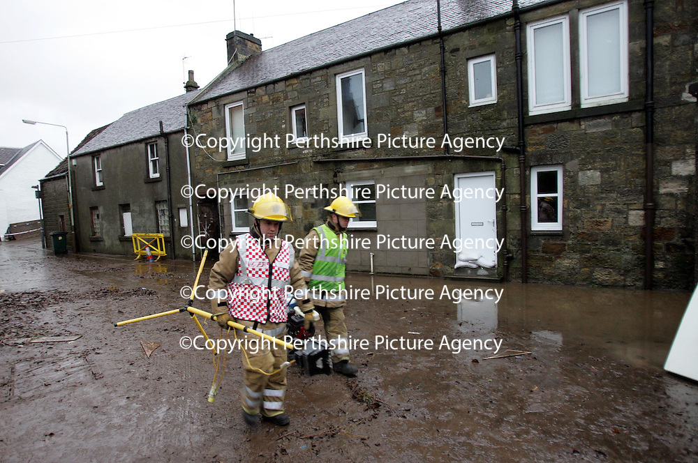 Firefighters clean up the mess in Milnathort after the River Queich burst it's banks flooding the town last night (Wednesday 13.12.06) The houses pictured behind the firefighters were under about 4 feet of water at the height of the flooding last night.<br />