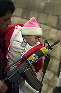 6 months old Palestine, is held close to the weapon of her father Riad Karmi, who was killed in an explosion in the West Bank town of Tulkarem January 14, 2002.