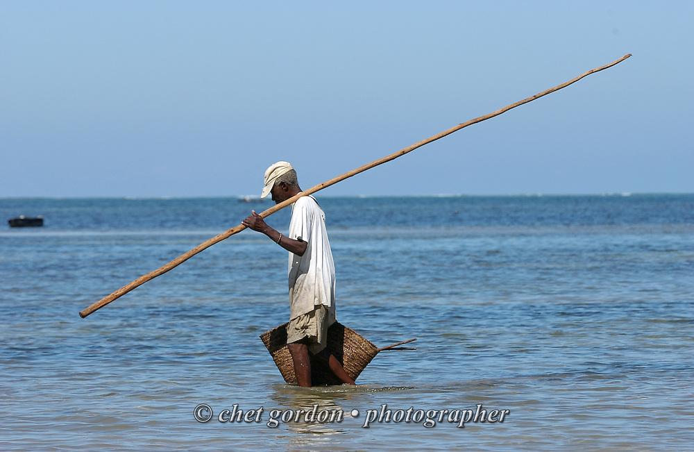 A Kenyan fisherman walks in the surf at Bamburi Beach in Mombasa, Kenya on Saturday, May 20, 2006.