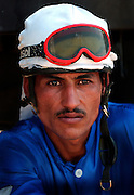 BAGHDAD, IRAQ - SEPTEMBER 24: An Iraqi Jockey prepares for the third race of the September 24, 2003 race lineup at the Abu Ghraib horse racing track in western Baghdad, Iraq. The track is open for racing three times a week (Sun, Wed, & Fri) and races are run on a dirt track.  Unlike in many other Muslim countries however, gambling is the primary draw for Iraqis attending the races.