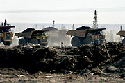 Fort McMurray, Alberta, CAN, June 14th 2007: A worker walks between huge dumpsters at a Syncrude oil sand field in Fort McMurray. The traditional oil sand mining is very intrusive to the nature as it is a day mine process, requiring the top soil to be removed.<br /> A new mining process involving steam injection is less intrusive, but both processing methods release huge amounts of CO2, making the net energy gain marginal. A recent tax rise by the Alberta government have caused Canadas second largest natural gas producer to consider cancelling oil sand projects.