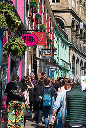 Tourists walking past shops on historic Victoria Street in Edinburgh Old town, Scotland, UK