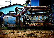 Local resting by the docks against a rusty train on Big Corn Island in Nicaragua.