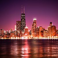 Photo of Chicago skyline at night with a violet sky. Includes the famous John Hancock Center skyscraper one of the tallest buildings in the world. Photo is large high resolution and was taken in 2012.