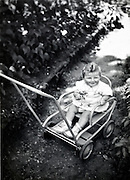 smiling toddler sitting in stroller France 1900s