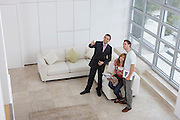 Real estate agent showing couple new home elevated view