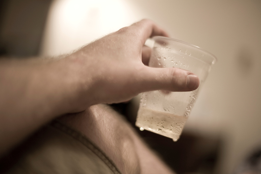 A man's hand holding a plastic cup in a motel room. Condensation drips off the bottom of the cup.