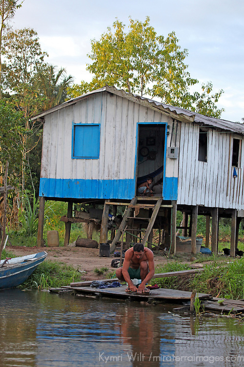 South America, Brazil, Amazon. Young boy watches from inside as father tends to chores on riverbank.