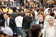 young adult man talking on his mobile phone while walking in a big crowded street Tokyo Japan
