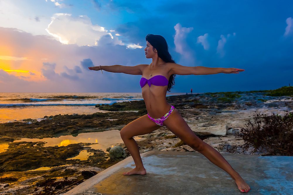 A woman at sunrise doing yoga along the Caribbean Sea at Akumal, Riviera Maya, Mexico.