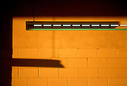Green fluorescent light and orange wall at sunrise