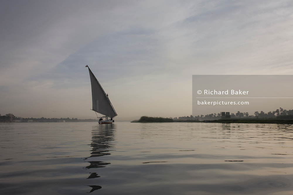 A scene of a distant felucca sailing boat on the River Nile at Luxor, Nile Valley, Egypt. Feluccas are ancient Egyptian sail boats which were used in ancient times as a primary mode of transport and are the only type of boat that is still used extensively in the country.