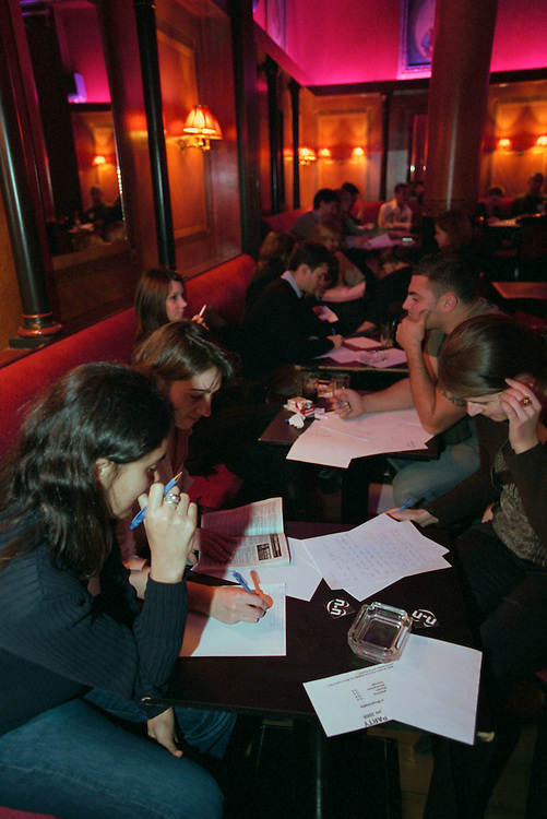"""Participants at a """"Quiet Party,"""" a soirée at La Villa where there is absolute silence for two hours and everyone must communicate by writing notes. Then the music is turned on and the evening continues on the dance floor..Paris, France. 07/12/2005.Photo © J.B. Russell"""