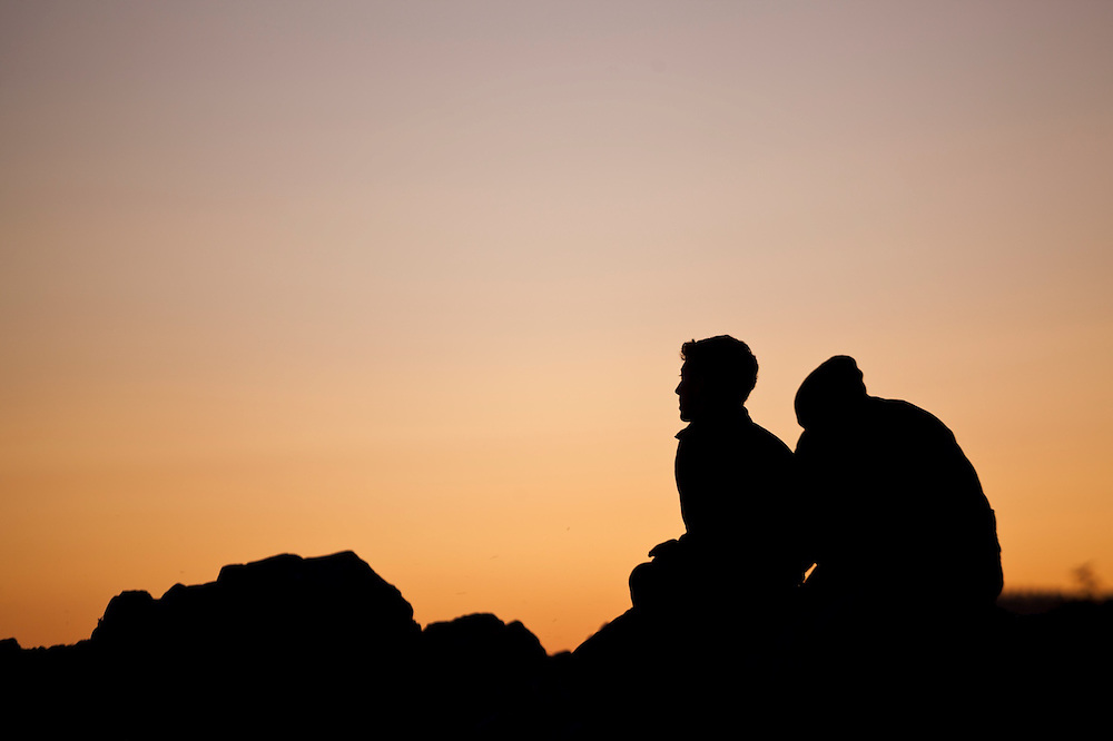 Henry (left) and Zach Podell-Eberhardt watch the sunset from a beach on the West Coast Trail, British Columbia, Canada.