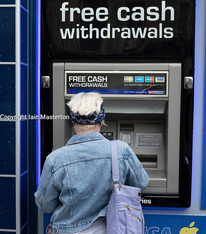 Woman using ATM machine with free cash withdrawals services Scotland, UK