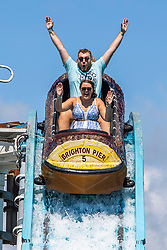 © Licensed to London News Pictures. 02/08/2020. Brighton, UK. Members of the public take a ride on one of the attractions on the Brighton Palace Pier in Brighton and Hove. Photo credit: Hugo Michiels/LNP