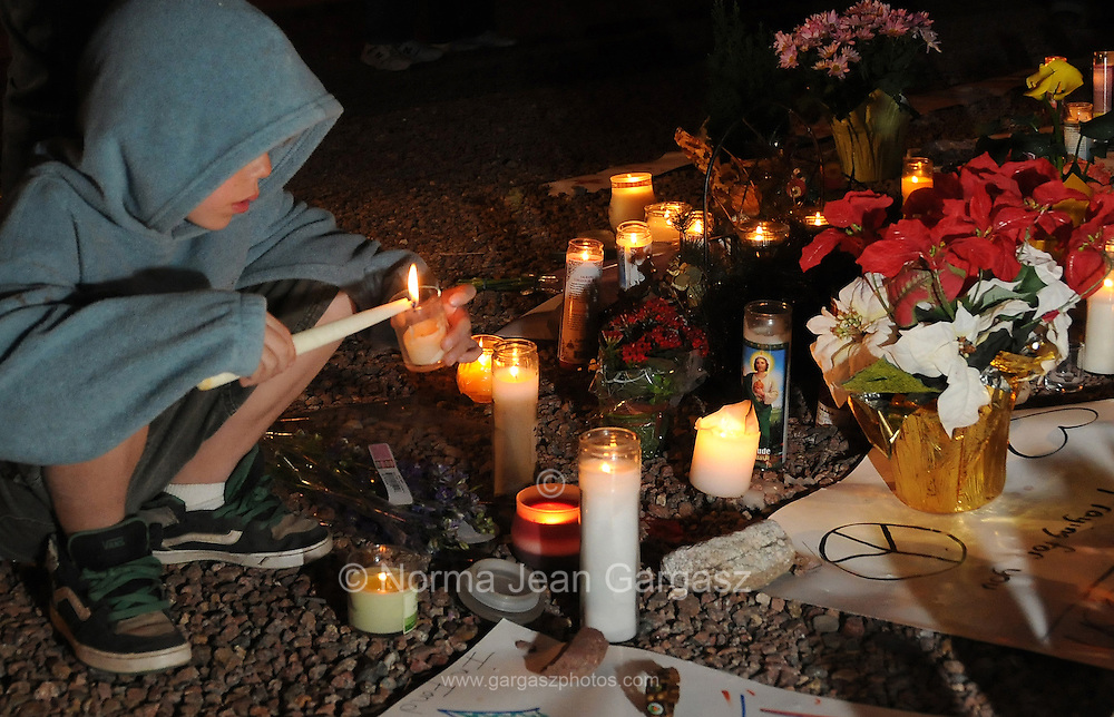 A memorial was created outside of the office of Arizona Congresswoman, Gabrielle Giffords, who is recovering from a gunshot wound to the head that she sustained on January 8, 2011, in Tucson, Arizona, USA.  Six people died in the attack outside of a grocery store.  Ben Canfield, 9, lights a candle.