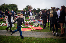 © Licensed to London News Pictures. 26/10/2017. Epsom, UK. A group of women stand next to floral tributes at the  funeral of Tom 'Tomboy' Doherty the nephew of Big Fat Gypsy Weddings star Paddy Doherty, at Epsom Cemetery in Epsom, Surrey. Tom Doherty was 17 when he was killed in a car crash in South Nutfield in Surrey on October 9. He had passed his driving test just days earlier. Photo credit: Ben Cawthra/LNP
