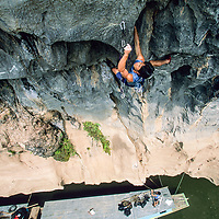 Tamotsu Sugino climbs unnamed 5.12d from boat on Nam Ou River, Ban Pak Ou, Luang Phrabang, Laos