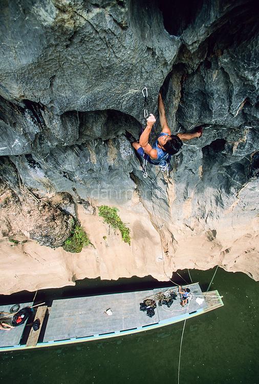 Tamotsu Sugino climbs unnamed 5.12d from boat on Nam Ou River, Ban Pak Ou, Luang Phrabang, Laos