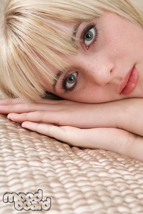 Portrait of teenage girl (16-17) lying on bed