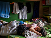 28 JANUARY 2018 - LEGAZPI, ALBAY, PHILIPPINES: Girls sleep in a classroom at the evacuation shelter for people from Barangay (community) Matanag in Albay Central School in Legazpi. People from the community have been in the shelter since Mayon volcano started erupting two weeks ago. There are about 500 families at the shelter, around 2,000 people. More than 80,000 people have been evacuated from communities around the volcano and are living in shelters and camps outside of the evacuation zone. The Philippine government is preparing to house the people for up to three months.      PHOTO BY JACK KURTZ
