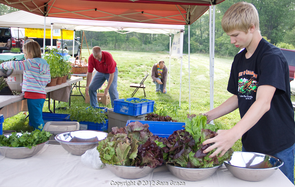 A family farms works to prepare their stand for the first outdoor Howe Meadow Farmers Market of 2012 in Peninsula, OH.