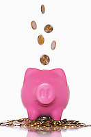 Coins pouring into overflowing piggy bank